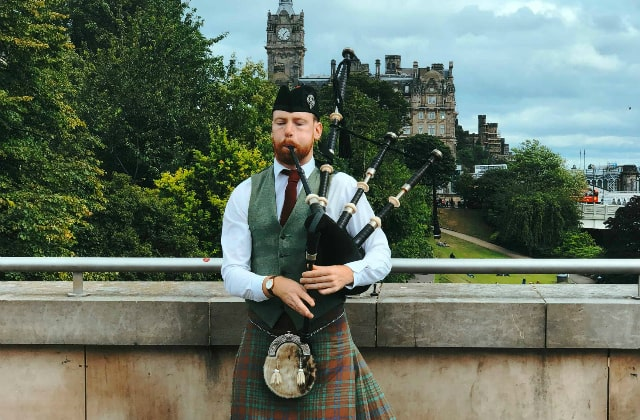 Scotsman in national outfit playing the bagpipes in Edinburgh